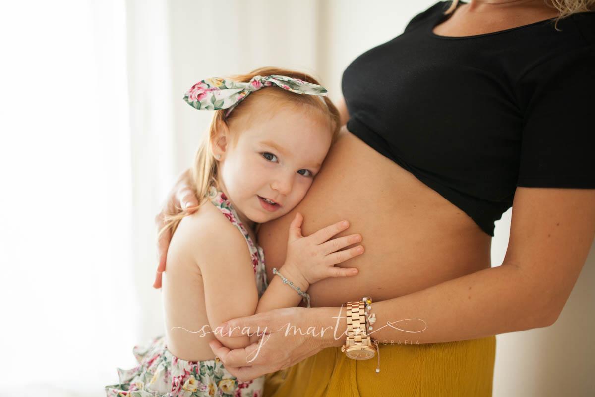 niña tocando barriga madre