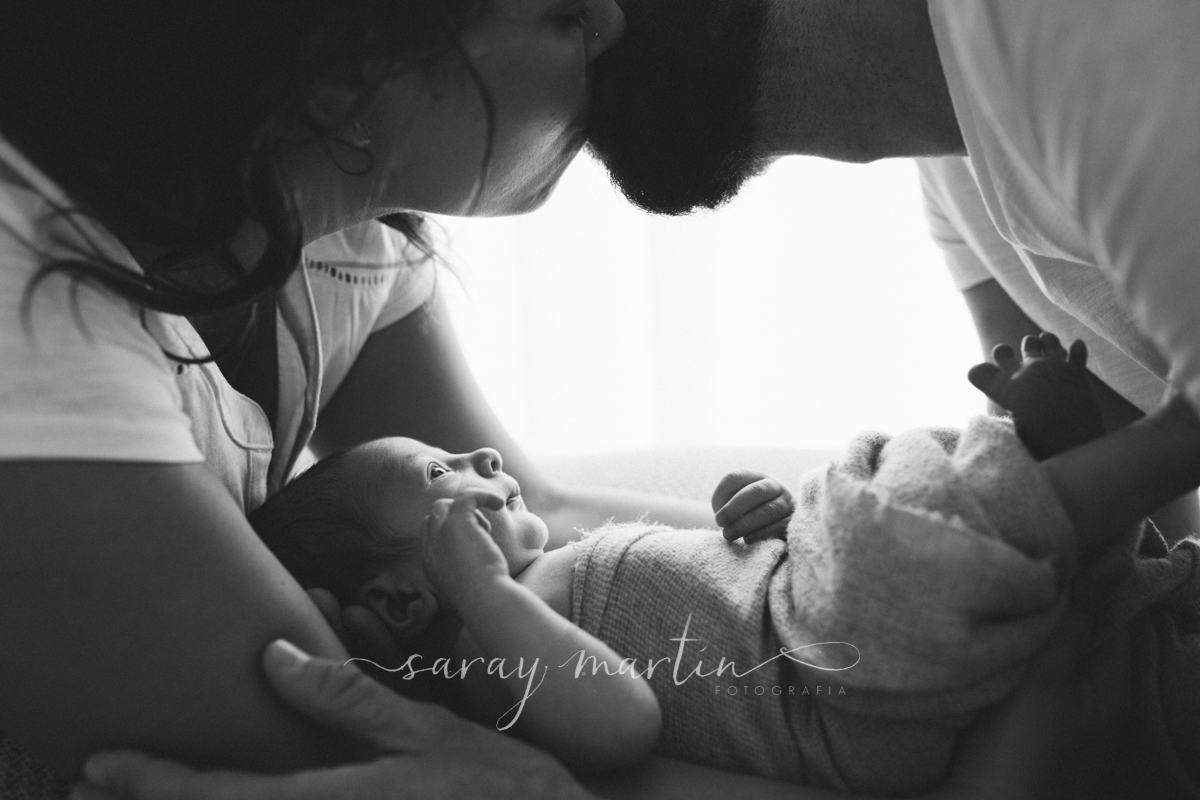 bebe tumbado mirando a padres